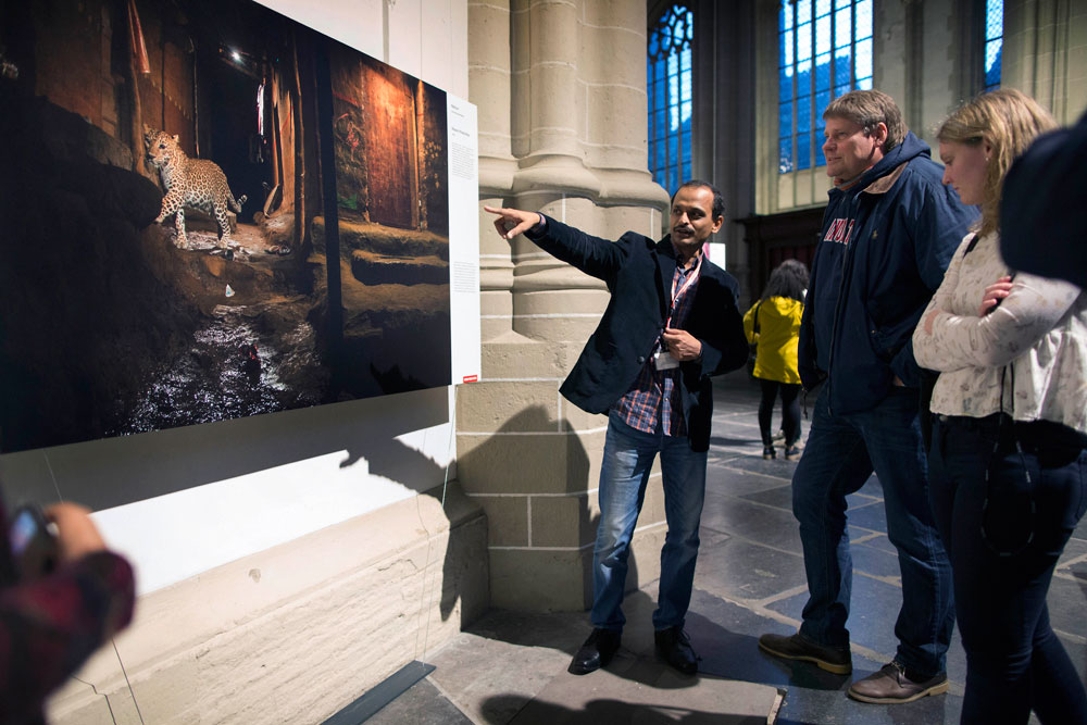 Nayan Khanolkar talks about his prize-winning image 'Alley Cat' to visitors at the Canon Night, organized by the World Press Photo ©Werry Crone / Hollandse Hoogte